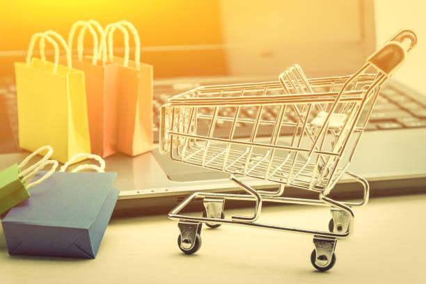 online-shopping / e-commerce und lieferung service konzept: papier, einkaufstaschen, einen einkaufswagen oder trolley und laptop-tastatur zeigt kunden bestellung dinge von händler-websites im internet. - kostenlose webseite stock-fotos und bilder