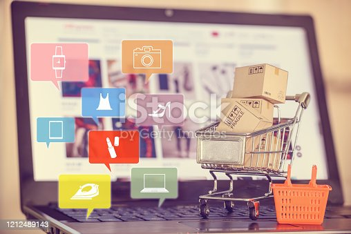 Box / carton with shopping cart, a grocery basket on a laptop keyboard, depicts consumers / customers / buyer buy goods and service from office or home