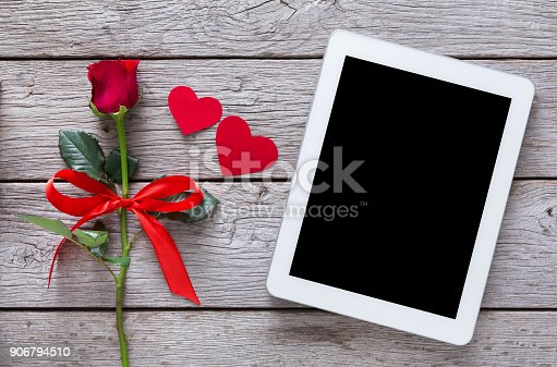 istock Online shopping holiday background, tablet screen, rose flower and paper hearts on rustic wood 906794510