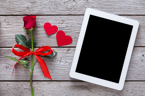 Online shopping holiday background, tablet screen, rose flower and paper hearts on rustic wood