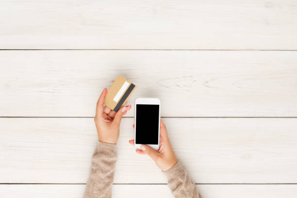 Online shopping in internet concept Online shopping in internet concept. Woman using credit card and blank smartphone, white wooden table background, top view phone charging stock pictures, royalty-free photos & images