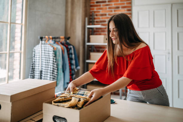 Online shopping makes happy a lot of people Woman packing item that she sells online clothes in box stock pictures, royalty-free photos & images