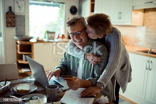 Close up of a mature couple doing online shopping in the morning