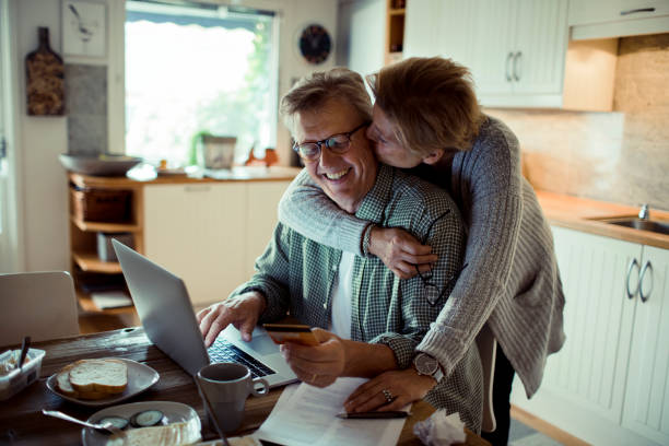 Online Shopping Close up of a mature couple doing online shopping in the morning mature couple stock pictures, royalty-free photos & images