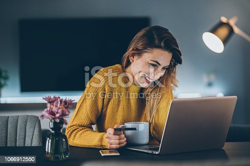 Young woman shopping online with credit card and lap top at home