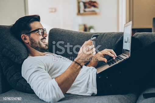 Smiling man lying on the couch and shopping online with credit card and laptop