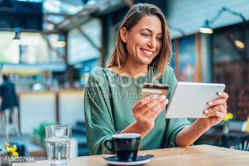 Young woman shopping online in cafe using digital tablet and credit card