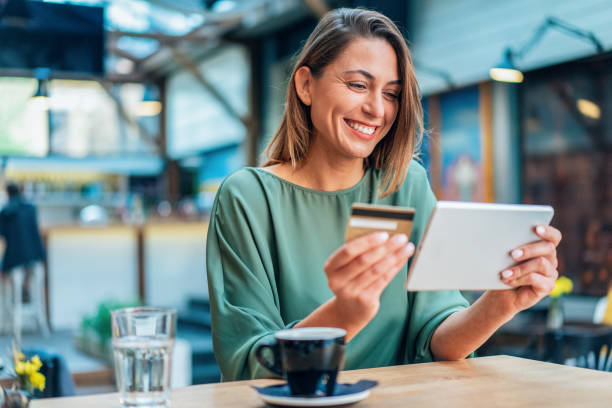 Online shopping Young woman shopping online in cafe using digital tablet and credit card credit card purchase stock pictures, royalty-free photos & images