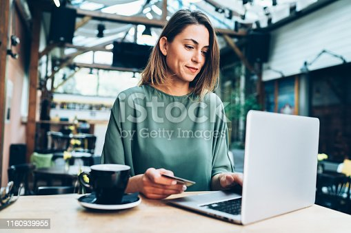 Young woman shopping online in cafe using lap top and credit card