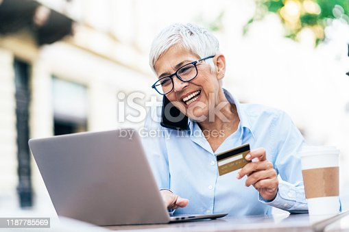 Senior business woman using lap top and credit card outdoor