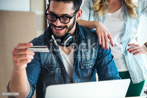 Man shopping online and holding a credit card.