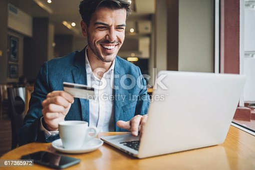 Smiling man sitting in cafe, holding a credit card and typing on a laptop.