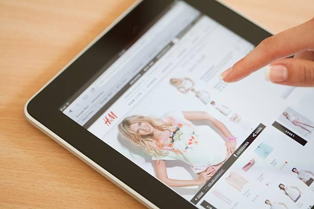 shopping online con ipad in h & m negozio - paypal foto e immagini stock
