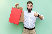 Online shopping. Young adult businessman thumbs up and looking at camera with surprised face.