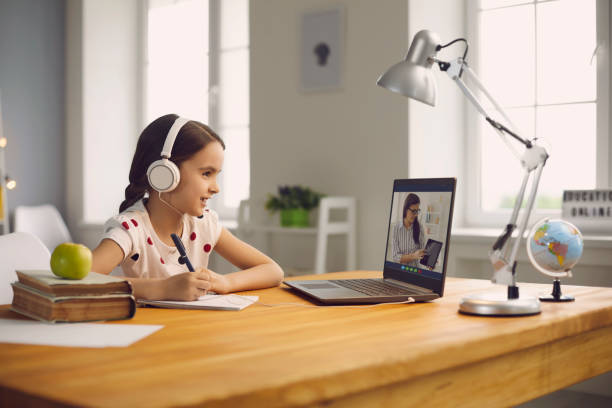 Online student education. Schoolgirl listens to a lecture of a teacher using a laptop video call lesson sitting at a table at home. stock photo