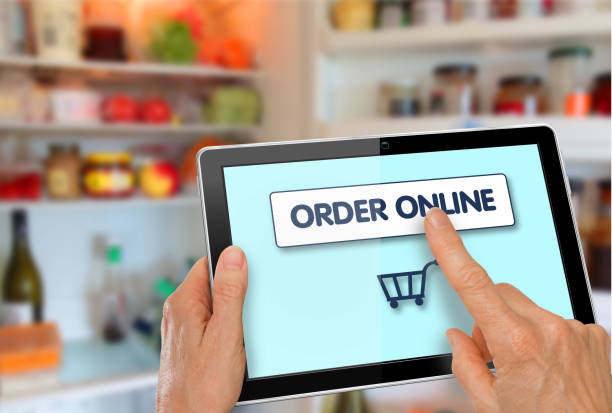Online Supermarket Shopping Hands with computer tablet shopping cart stock photo