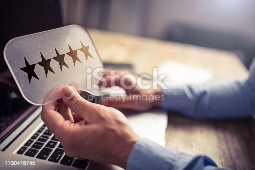 Man working on a laptop. He is holding a message bubble symbol showing five star ration