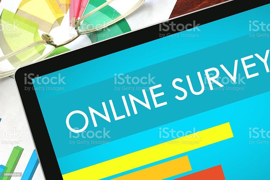 Online Survey written on a tablet. Web marketing concept. stock photo