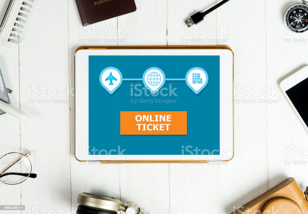 Online Travel Ticket booking on tablet with travel accessories stock photo