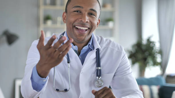 online video chat with patient by african-american doctor, camera view - webcam stock photos and pictures