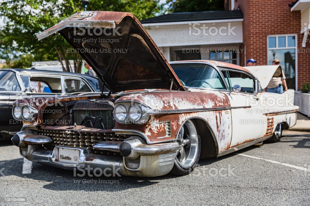 Onlookers inspect a rusty classic Cadillac parked on display at the Matthews Auto Reunion stock photo
