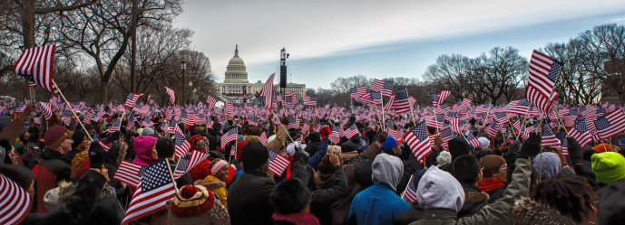 Washington, USA - January 21, 2012: Onlookers holding American flags on the National Mall observe Inauguration of Barack Obama as the President in Washington, DC on January 21, 2013. Barack Obama is the 44th president of USA and the first African American to hold presidential office in the United States.