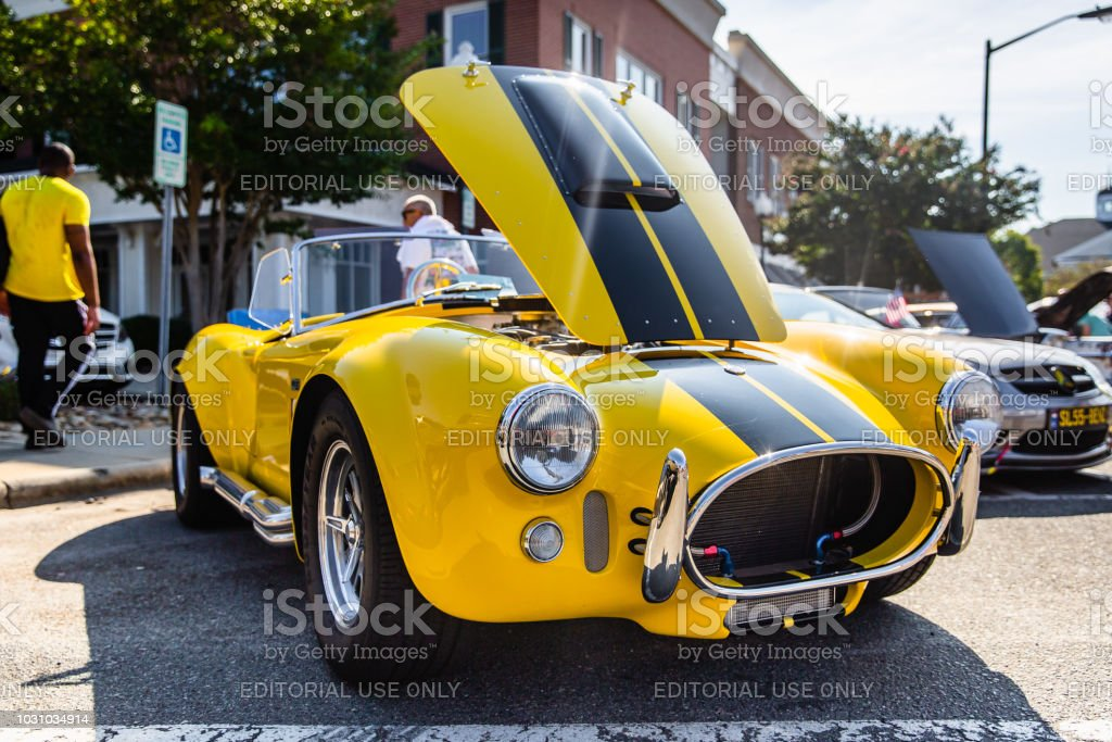 Onlookers pass a Shelby Cobra on display at the Matthews Auto Reunion stock photo
