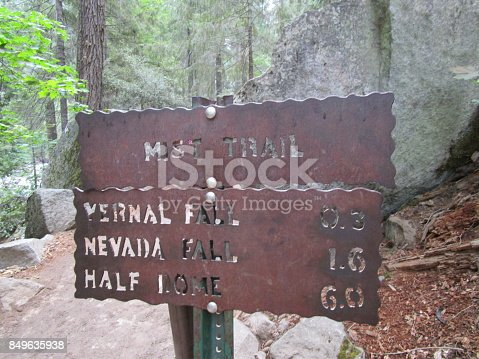 Rusty old metal hiking distance sign for Yosemite Mist trails with a large granite boulder and pine trees in the forest background.