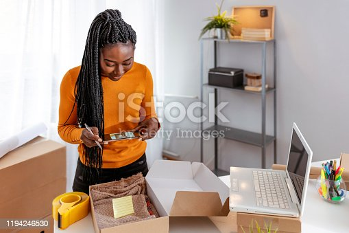 Young start up small business African-American owner packing cardboard box at workplace. Freelance woman seller prepare parcel box of product for deliver to customer. Online selling, e-commerce, shipping concept