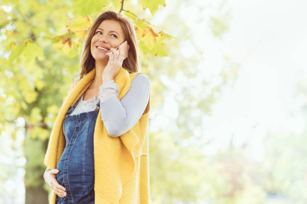 nur noch wenige tage, bis das baby kommt - latzhose für schwangere stock-fotos und bilder