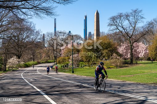 Manhattan, New York, NY, USA - April 6, 2020: Only a few people still exercising in Central Park in front of Manhattan Skyline, deserted because of Coronavirus Outbreak. A single bicyclist riding along the deserted East Drive.