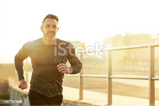 Shot of a mature man running on the promenade as part of his exercise routine