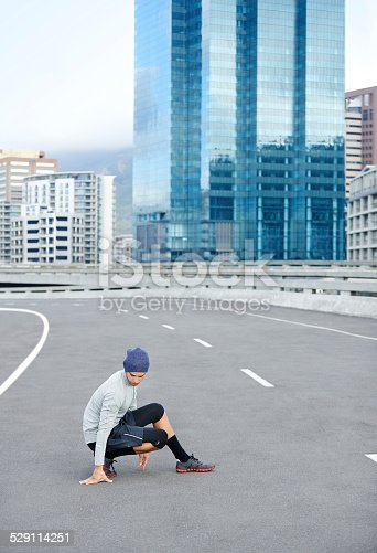 Shot of a young male jogger stretching on an empty street before a run