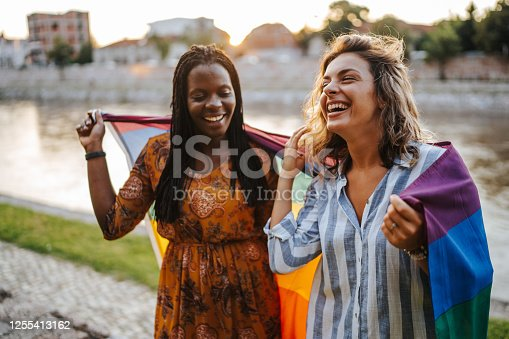 Young multi ethnic lesbian couple with rainbow flag on city quay
