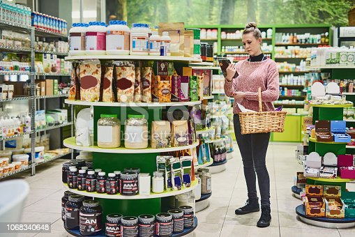 Shot of a young woman browsing for goods on the shelves in a health store