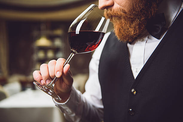 Only truly connoisseur can feel fragrance Close up. Bearded serious man is inhaling aroma of scarlet wine with pleasure critic stock pictures, royalty-free photos & images