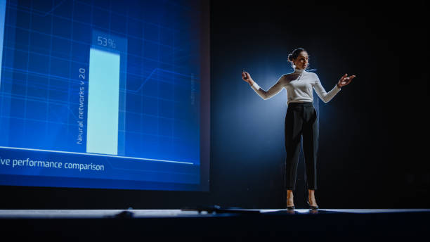 On-Stage Successful Female Speaker Presents Technological Product, Uses Remote Control for Presentation, Showing Infographics, Statistics Animation on Screen. Live Event / Device Release. stock photo