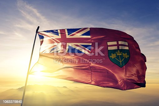 Ontario province of Canada flag on flagpole textile cloth fabric waving on the top sunrise mist fog