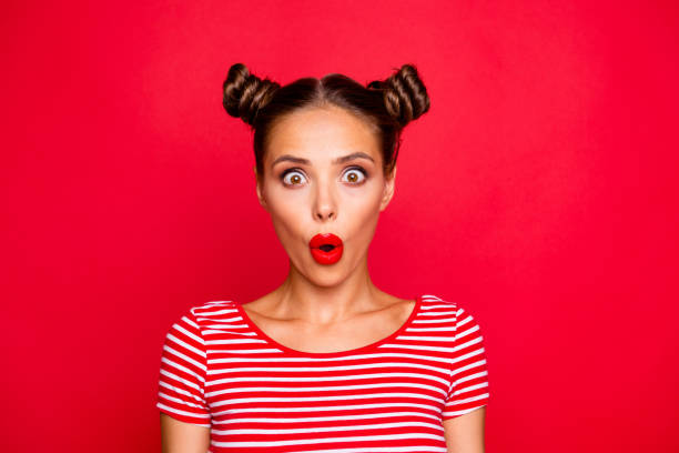 Oops! Closeup portrait of shocked impressed model with red lips with unexpected unbelievable reaction looking at camera with wide open eyes and mouth isolated on red background stock photo