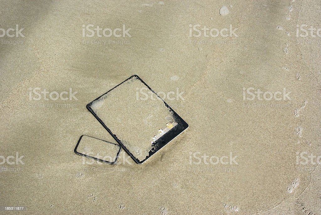 oops; digital tablet and smart phone submerged in wet sand stock photo