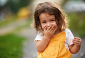 Little girl with brown hair outdoors, covering her mouth laughing
