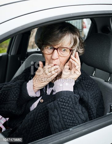 A senior woman driver in her car covers her mouth in embarrassment at being caught using a smart phone.
