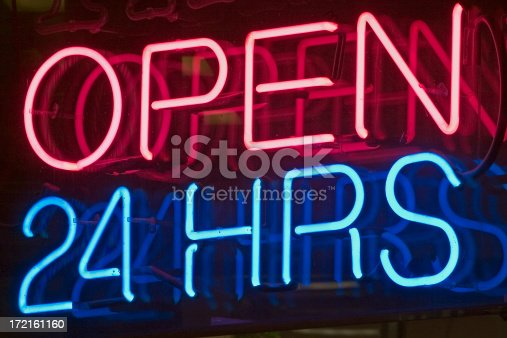 Neon sign shot at night in window depicts Open 24 hours.
