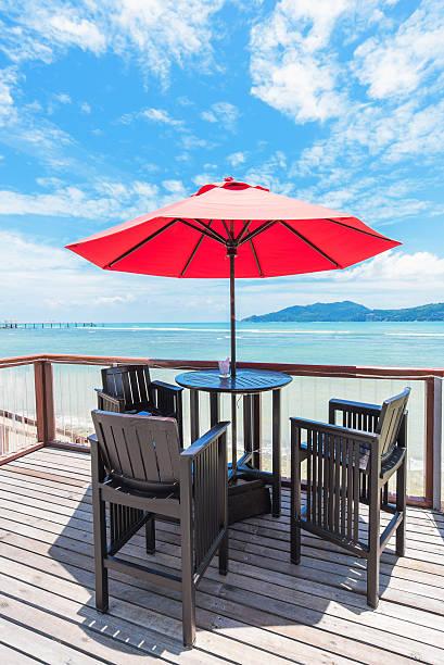 open-air-café-bar auf der terrasse mit meerblick - sonnenschirm terrasse stock-fotos und bilder