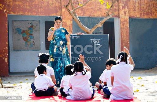 Teacher teaching kids on blackboard at school campus