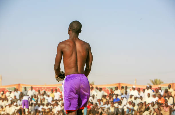 Open air traditional Nubian wrestling in Khartoum, Sudan Khartoum, Sudan - February 19, 2010: Traditional Nubian wrestling in Khartoum, Sudan. Every Friday people gather in open public spaces to practice and watch Nubian wrestling. This traditional form of fight is named after the Nubian tribes from Kordofan though it is practiced by people from other ethnic backgrounds too. Khartoum is the capital and largest city of Sudan, located at the confluence of the White Nile, flowing north from Lake Victoria in Uganda, and the Blue Nile, flowing west from Ethiopia. Khartoum is composed of 3 cities: Khartoum proper, Khartoum North and Omdurman. omdurman stock pictures, royalty-free photos & images