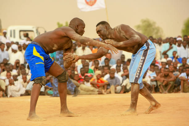 Open air traditional Nubian wrestling in Khartoum, Sudan Khartoum, Sudan - May 28, 2010: Traditional Nubian wrestling in Khartoum, Sudan. Every Friday people gather in open public spaces to practice and watch Nubian wrestling. This traditional form of fight is named after the Nubian tribes from Kordofan though it is practiced by people from other ethnic backgrounds too. Khartoum is the capital and largest city of Sudan, located at the confluence of the White Nile, flowing north from Lake Victoria in Uganda, and the Blue Nile, flowing west from Ethiopia. Khartoum is composed of 3 cities: Khartoum proper, Khartoum North and Omdurman. omdurman stock pictures, royalty-free photos & images