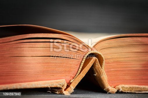 537881816 istock photo Open ancient book on wooden table close up 1094597940
