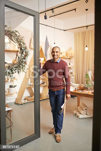 Shot of an entrepreneurial young man standing by the open door of a store