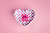 Open and closed gift box of pink color with a bow. On a pink background, top view
